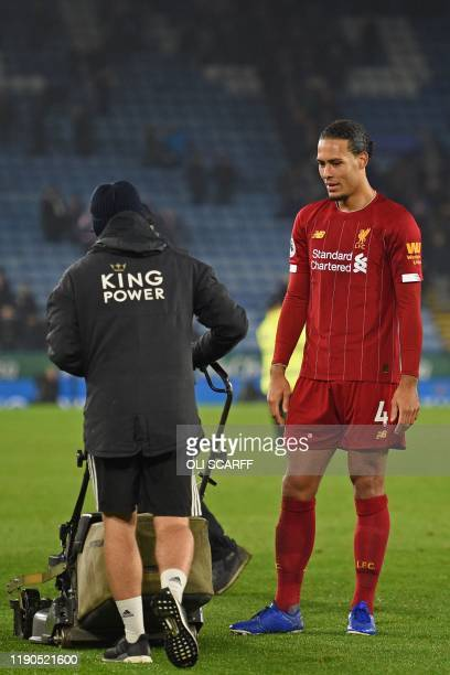 Liverpool's Dutch defender Virgil van Dijk checks out the lawn mower on the pitch after the English Premier League football match between Leicester...