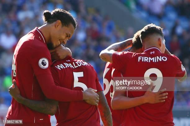 Liverpool's Dutch defender Virgil van Dijk embraces Liverpool's Dutch midfielder Georginio Wijnaldum after the final whistle of the English Premier...