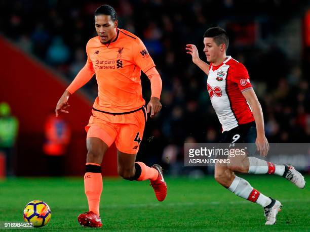 Liverpool's Dutch defender Virgil van Dijk is challenged by Southampton's Argentinian striker Guido Carrillo during the English Premier League...