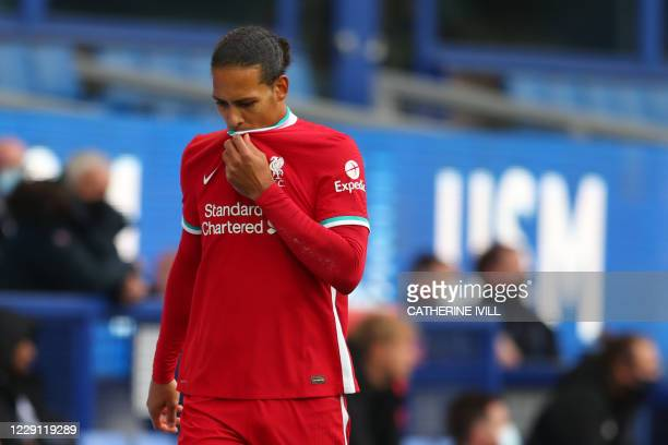 Liverpool's Dutch defender Virgil van Dijk leaves the field injured during the English Premier League football match between Everton and Liverpool at...