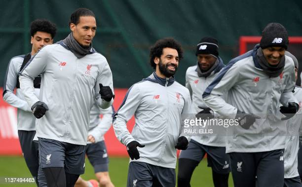 Liverpool's Dutch defender Virgil van Dijk Liverpool's Egyptian midfielder Mohamed Salah Liverpool's Dutch midfielder Georginio Wijnaldum and...
