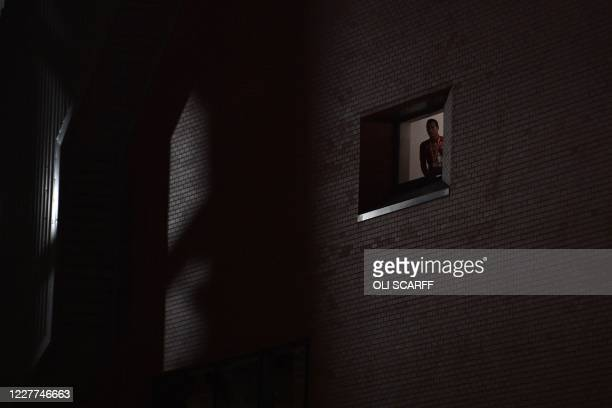 Liverpool's Dutch defender Virgil van Dijk looks out from a window in Anfield stadium at Liverpool fans celebrating outside the ground in Liverpool...