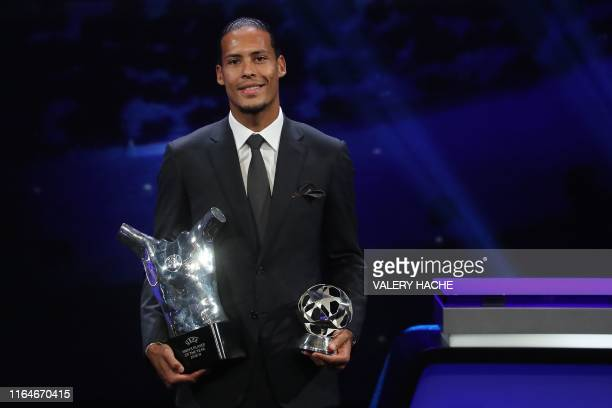 TOPSHOT Liverpool's Dutch defender Virgil van Dijk poses with his trophies of Best Men's player in Europe of the Year and Best Defender at the end of...