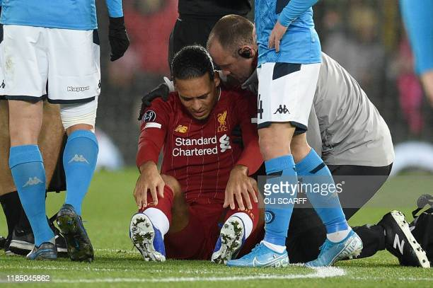 Liverpool's Dutch defender Virgil van Dijk receives medical treatment during the UEFA Champions league Group E football match between Liverpool and...