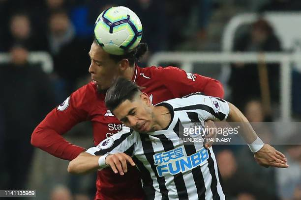 Liverpool's Dutch defender Virgil van Dijk vies with Newcastle United's Spanish striker Ayoze Perez to header the ball during the English Premier...