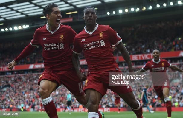 Liverpool's Dutch midfielder Georginio Wijnaldum celebrates scoring his team's first goal with Liverpool's Brazilian midfielder Roberto Firmino...