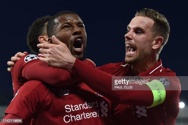 Liverpool's Dutch midfielder Georginio Wijnaldum celebrates with Liverpool's English midfielder Jordan Henderson after scoring their third goal...