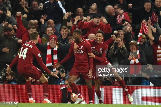 Liverpool's Dutch midfielder Georginio Wijnaldum celebrates with Liverpool's English midfielder Jordan Henderson and Liverpool's English defender...