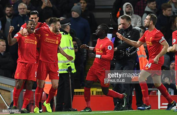 Liverpool's Dutch midfielder Georginio Wijnaldum celebrates with teammates after scoring the opening goal of the English Premier League football...