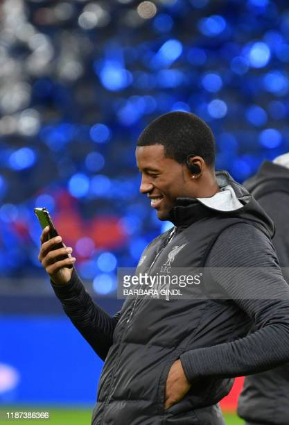 Liverpool's Dutch midfielder Georginio Wijnaldum looks at his smartphone during a place inspection on the eve of the UEFA Champions League group E...