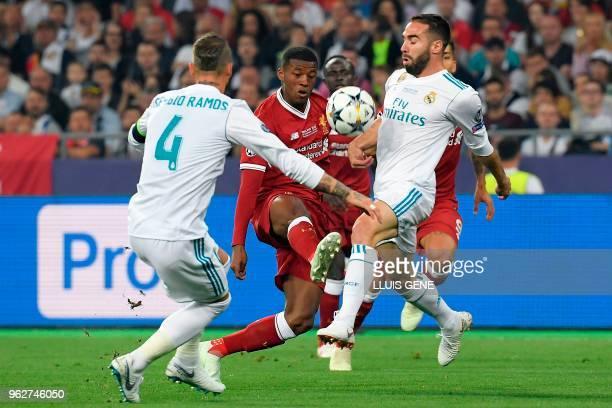 Liverpool's Dutch midfielder Georginio Wijnaldum vies with Real Madrid's Spanish defender Sergio Ramos and Real Madrid's Spanish defender Dani...