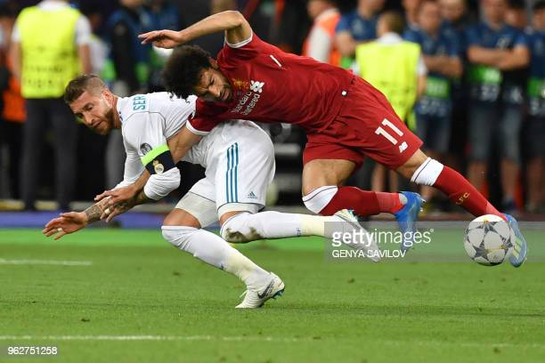 TOPSHOT Liverpool's Egyptian forward Mohamed Salah falls with Real Madrid's Spanish defender Sergio Ramos leading to Salah being injured during the...