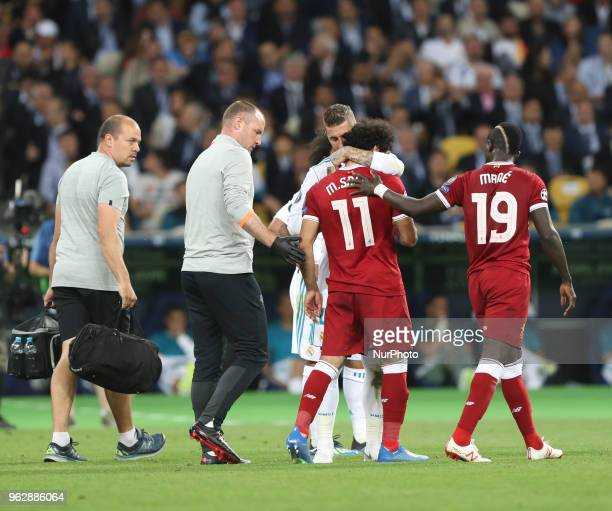Liverpool's Egyptian forward Mohamed Salah is comforted by Real Madrid's Sergio Ramos as he leaves the pitch after injury during the UEFA Champions...