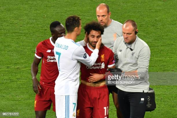 TOPSHOT Liverpool's Egyptian forward Mohamed Salah is comforted by team members and Real Madrid's Portuguese forward Cristiano Ronaldo as he leaves...