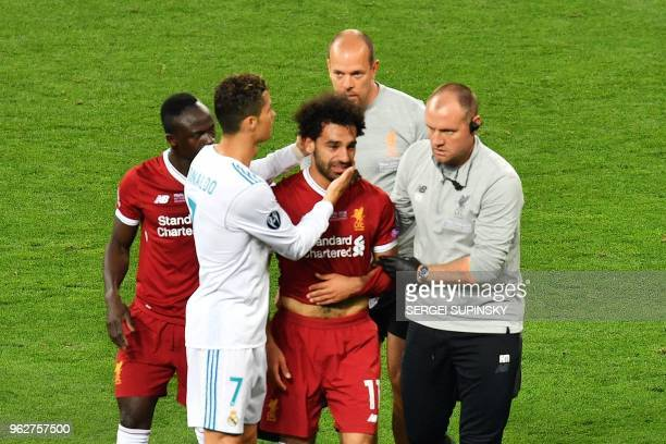 Liverpool's Egyptian forward Mohamed Salah is comforted by team members and Real Madrid's Portuguese forward Cristiano Ronaldo as he leaves the pitch...