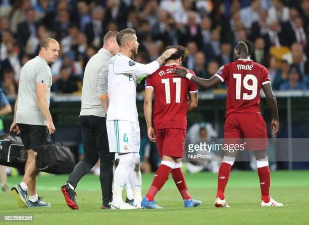 Liverpool's Egyptian forward Mohamed Salah is comforted by team members and Real Madrid's Sergio Ramos as he leaves the pitch after injury during the...