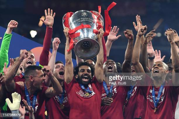 Liverpool's Egyptian forward Mohamed Salah raises the European Champion Clubs' Cup as he celebrates with teammates winning the UEFA Champions League...