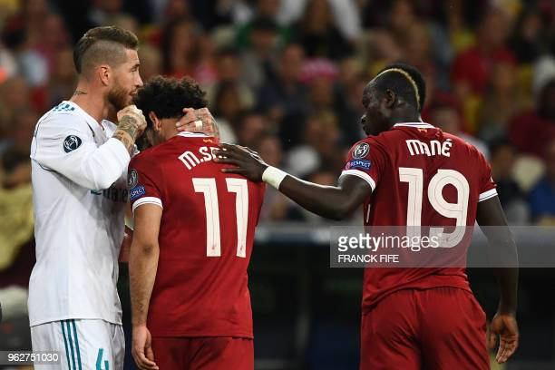 Liverpool's Egyptian forward Mohamed Salah reacts as he leaves the pitch after an injury while Liverpool's Senegalese midfielder Sadio Mane and Real...