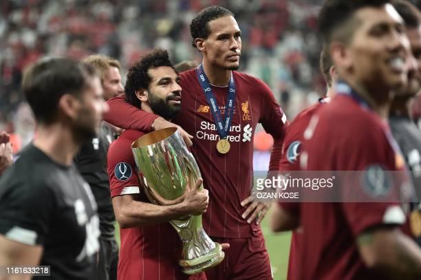 Liverpool's Egyptian midfielder Mohamed Salah and Liverpool's Dutch defender Virgil van Dijk pose with the trophy after winning the UEFA Super Cup...