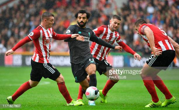 Liverpool's Egyptian midfielder Mohamed Salah battles for space against Sheffield United's Englishborn Northern Irish midfielder Oliver Norwood and...