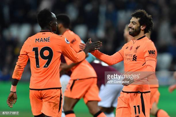 Liverpool's Egyptian midfielder Mohamed Salah celebrates after scoring with Liverpool's Senegalese midfielder Sadio Mane during the English Premier...