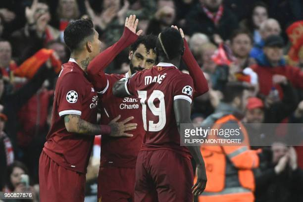 Liverpool's Egyptian midfielder Mohamed Salah celebrates after scoring with Liverpool's Brazilian midfielder Roberto Firmino and Liverpool's...