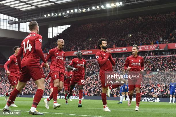 TOPSHOT Liverpool's Egyptian midfielder Mohamed Salah celebrates with teammates after scoring their second goal during the English Premier League...