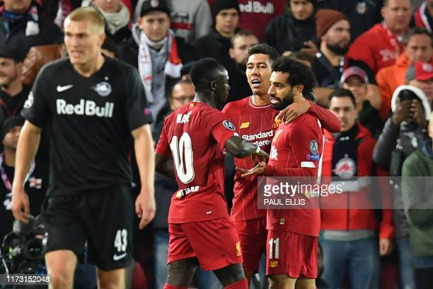 Liverpool's Egyptian midfielder Mohamed Salah celebrates with teammates after scoring their third goal during the UEFA Champions league Group E...