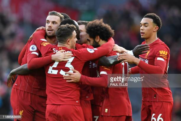 Liverpool's Egyptian midfielder Mohamed Salah celebrates with teammates after scoring his team's first goal during the English Premier League...
