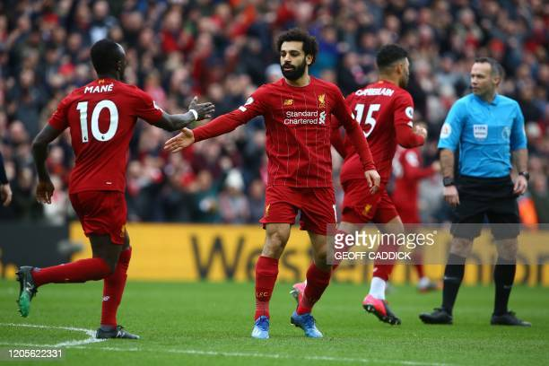 Liverpool's Egyptian midfielder Mohamed Salah celebrates with teammates after he scoring his team's first goal during the English Premier League...