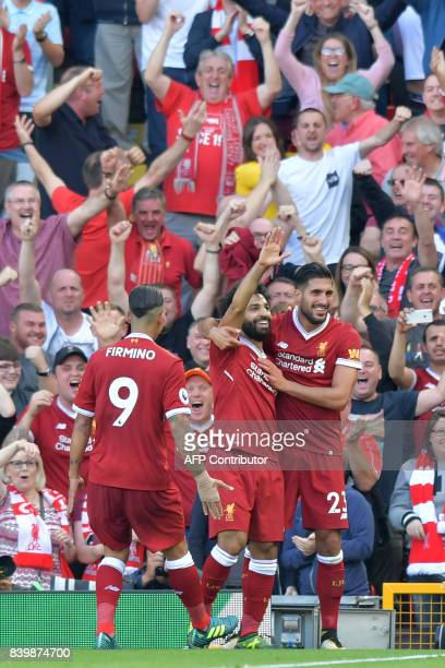 Liverpool's Egyptian midfielder Mohamed Salah celebrates with teammates after scoring their third goal during the English Premier League football...