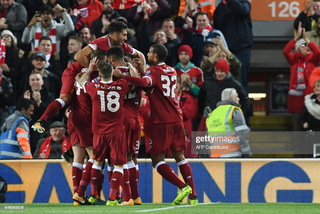 Liverpool's Egyptian midfielder Mohamed Salah celebrates with teammates after scoring during the UEFA Champions League Group E football match between Liverpool and Sevilla at Anfield in Liverpool, north-west England on September 13, 2017. / AFP PHOTO / Paul ELLIS