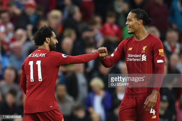 Liverpool's Egyptian midfielder Mohamed Salah celebrates with Liverpool's Dutch defender Virgil van Dijk after scoring the team's second goal during...