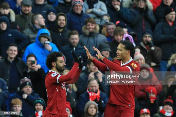 Liverpool's Egyptian midfielder Mohamed Salah celebrates with Liverpool's Dutch defender Virgil van Dijk scoring the team's first goal during the...