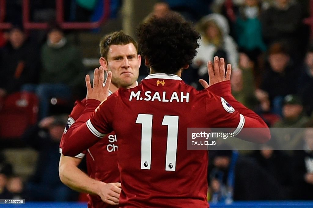 Liverpool's Egyptian midfielder Mohamed Salah (R) celebrates with Liverpool's English midfielder James Milner (L) after scoring their third goal from the penalty spot during the English Premier League football match between Huddersfield Town and Liverpool at the John Smith's stadium in Huddersfield, northern England on January 30, 2018. / AFP PHOTO / PAUL ELLIS / RESTRICTED TO EDITORIAL USE. No use with unauthorized audio, video, data, fixture lists, club/league logos or 'live' services. Online in-match use limited to 75 images, no video emulation. No use in betting, games or single club/league/player publications. /