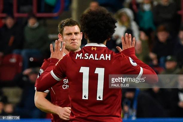 Liverpool's Egyptian midfielder Mohamed Salah celebrates with Liverpool's English midfielder James Milner after scoring their third goal from the...