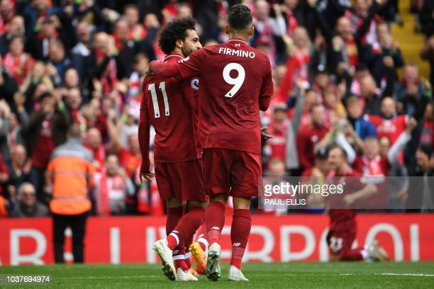 Liverpool's Egyptian midfielder Mohamed Salah celebrates with Liverpool's Brazilian midfielder Roberto Firmino after scoring the team's third goal...