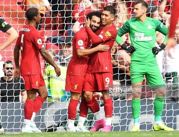 TOPSHOT Liverpool's Egyptian midfielder Mohamed Salah celebrates with Liverpool's Brazilian midfielder Roberto Firmino after scoring the team's third...