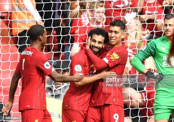 Liverpool's Egyptian midfielder Mohamed Salah celebrates with Liverpool's Brazilian midfielder Roberto Firmino after scoring the team's third goal...