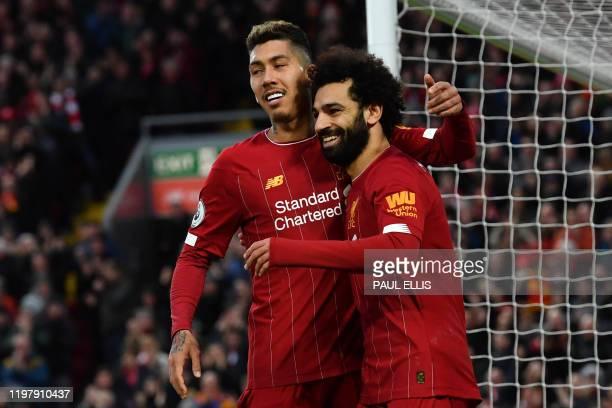 Liverpool's Egyptian midfielder Mohamed Salah celebrates with Liverpool's Brazilian midfielder Roberto Firmino after scoring his team's third goal...