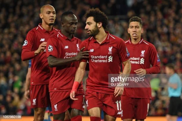 Liverpool's Egyptian midfielder Mohamed Salah celebrates with Liverpool's Senegalese striker Sadio Mane and Liverpool's Brazilian midfielder Fabinho...