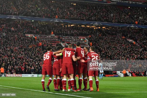 Liverpool's Egyptian midfielder Mohamed Salah celebrates with teammates scoring the opening goal during the UEFA Champions League first leg...