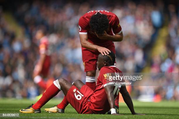 Liverpool's Egyptian midfielder Mohamed Salah consoles Liverpool's Senegalese midfielder Sadio Mane after he makes a dangerous challenge on...