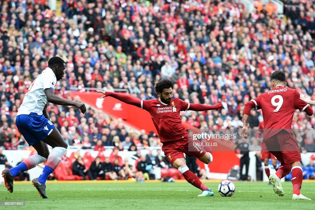 TOPSHOT - Liverpool's Egyptian midfielder Mohamed Salah (C) controls the ball during the English Premier League football match between Liverpool and Stoke City at Anfield in Liverpool, north west England on April 28, 2018. (Photo by Paul ELLIS / AFP) / RESTRICTED TO EDITORIAL USE. No use with unauthorized audio, video, data, fixture lists, club/league logos or 'live' services. Online in-match use limited to 75 images, no video emulation. No use in betting, games or single club/league/player publications. /