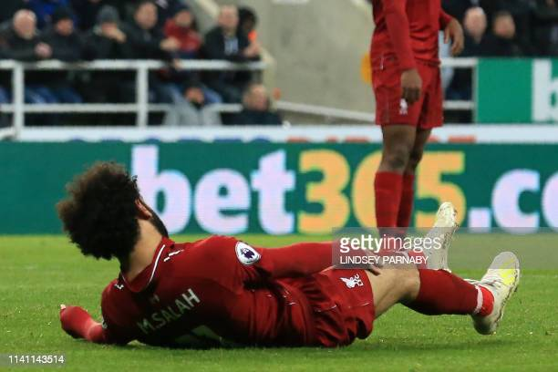 Liverpool's Egyptian midfielder Mohamed Salah falls to the ground after injuring himself in a challenge with Newcastle United's Slovakian goalkeeper...