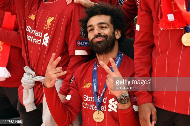 Liverpool's Egyptian midfielder Mohamed Salah gestures to the fans during an opentop bus parade around Liverpool northwest England on June 2 after...