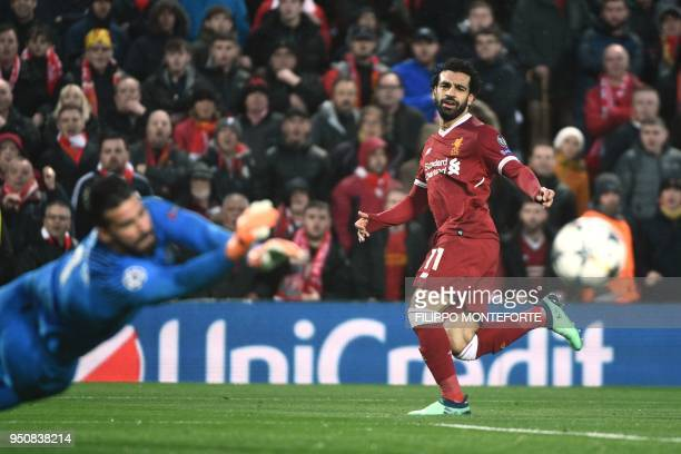 TOPSHOT Liverpool's Egyptian midfielder Mohamed Salah has a shot by Roma's Brazilian goalkeeper Alisson during the UEFA Champions League first leg...
