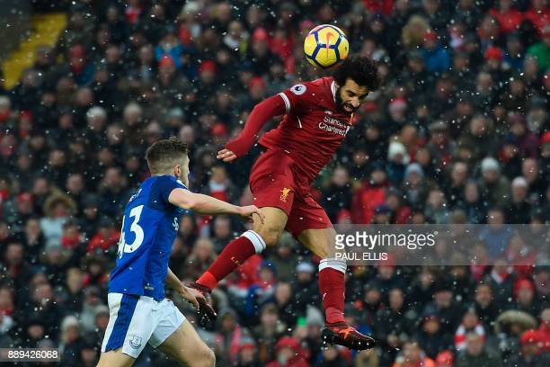 Liverpool's Egyptian midfielder Mohamed Salah heads the ball wide during the English Premier League football match between Liverpool and Everton at...