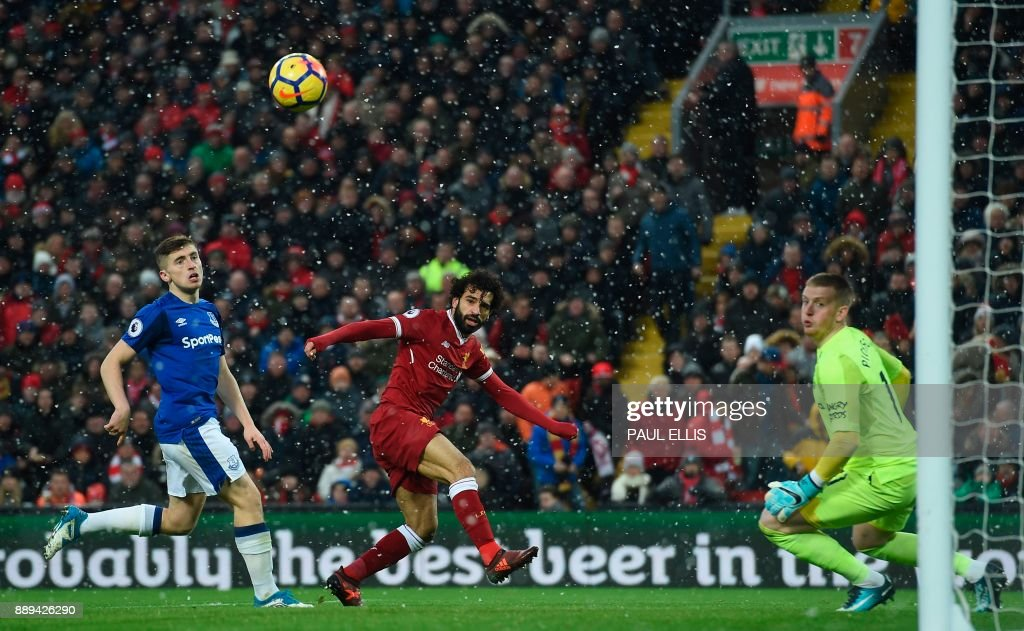 TOPSHOT - Liverpool's Egyptian midfielder Mohamed Salah (C) heads the ball wide during the English Premier League football match between Liverpool and Everton at Anfield in Liverpool, north west England on December 10, 2017. / AFP PHOTO / PAUL ELLIS / RESTRICTED TO EDITORIAL USE. No use with unauthorized audio, video, data, fixture lists, club/league logos or 'live' services. Online in-match use limited to 75 images, no video emulation. No use in betting, games or single club/league/player publications. /