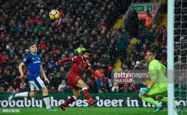 TOPSHOT Liverpool's Egyptian midfielder Mohamed Salah heads the ball wide during the English Premier League football match between Liverpool and...